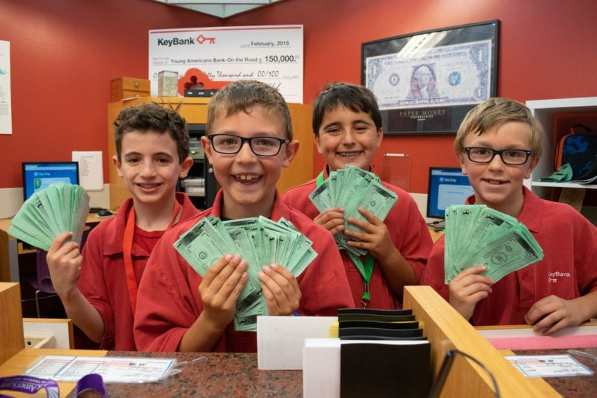 Summer Camp Bankers in Young AmeriTowne are shown holding cash
