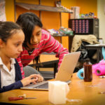 Two girls building a product prototype and looking at a laptop screen for Youthbiz